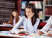 Mädchen-Lesebuch am Schreibtisch mit Freunden Lizenzfreies Stockfoto