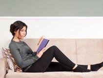 Mädchen-Lesebuch - stillstehend auf Couch Lizenzfreies Stockbild