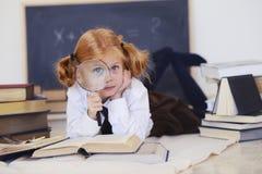 Mädchen liegt mit einem Vergrößerungsglas und Büchern Stockfotos