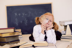Mädchen liegt mit einem Vergrößerungsglas und Büchern stockbild