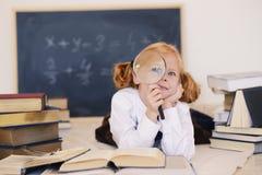 Mädchen liegt mit einem Vergrößerungsglas und Büchern stockfotografie