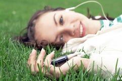 Mädchen liegt mit MP3-Player stockfoto