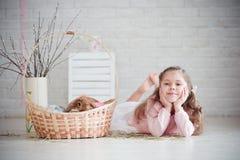 Mädchen liegt nahe einem Korb mit Kaninchen Stockfoto