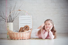 Mädchen liegt nahe einem Korb mit Kaninchen Lizenzfreie Stockfotos