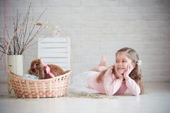 Mädchen liegt nahe einem Korb mit Kaninchen Stockbild