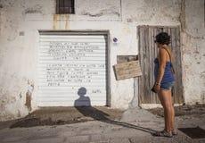 Mädchen liest das Gedicht, das auf Rollenfensterladen geschrieben wird Lizenzfreie Stockfotografie
