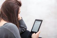 Mädchen liest ein Buch mit einem eBook Leser Stockbilder