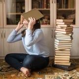 Mädchen müde von den Klassen Sitzen auf dem Boden bedeckt mit einem Buch nahe bei einem Stapel Büchern stockfoto