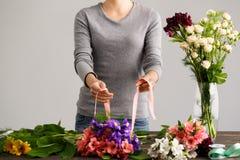 Mädchen machen Blumenstrauß über grauem Hintergrund Stockfoto