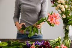 Mädchen machen einen Blumenstrauß über dem grauen Hintergrund und schneiden Stamm Stockbild