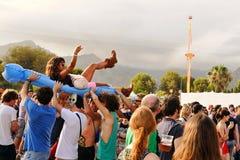 Mädchen macht den Körper, der über eine aufblasbare Matratze an Los Tiki Phantoms surft, Show an der FLUNKEREI mit einem Band zu  Stockbild