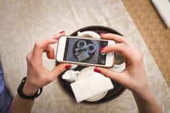 Mädchen macht ein Bild von zwei Schalen mit Kaffee, Nahaufnahme Stockbild