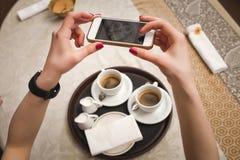 Mädchen macht ein Bild von zwei Schalen mit Kaffee, Nahaufnahme Stockfotografie