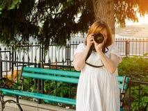 Mädchen macht Fotos auf Kamera auf dem Hintergrund der Bank im Park Stockfoto