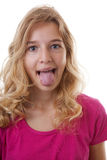Mädchen macht lustiges Gesicht in der Nahaufnahme über weißem Hintergrund Lizenzfreies Stockbild