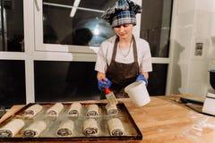 Mädchen macht selbst gemachte Brötchen, geschnittene Rollen der Teigrolle Ansicht von oben stockbilder