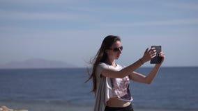 Mädchen macht selfie mit ihrem Telefon in der Zeitlupe auf dem Strand stock video