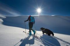 Mädchen macht Skibergsteigen mit seinem Hund stockfotos