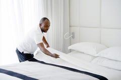 Mädchen Making Bed lizenzfreie stockfotografie