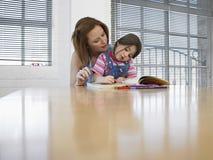 Mädchen-Malbuch während Mutter, die bei Tisch sie unterstützt Stockfotografie