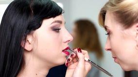 Mädchen malt ihren Lippenroten Lippenstift, den Make-upkünstler, der Make-upkunden in einem Salon tut stock video