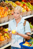 Mädchen am Markt, der Früchte wählt, übergibt Zitronen Stockbild