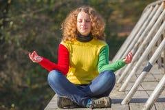 Mädchen meditiert auf der Brücke lizenzfreie stockfotos