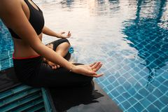 Mädchen meditiert bei Sonnenuntergang in Thailand nahe dem Pool stockbild