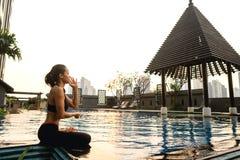 Mädchen meditiert bei Sonnenuntergang in Thailand nahe dem Pool lizenzfreies stockfoto
