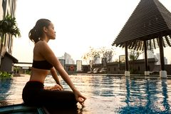 Mädchen meditiert bei Sonnenuntergang in Thailand nahe dem Pool lizenzfreie stockfotografie