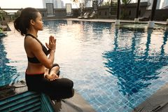 Mädchen meditiert bei Sonnenuntergang in Thailand nahe dem Pool stockbilder