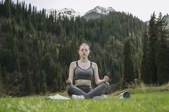 Mädchen meditiert in einer Lotoshaltung auf dem Hintergrund eines Berges Stockbild