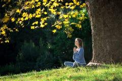 Mädchen meditiert, sitzend auf dem Gras unter einem Ahornbaum im Herbst lizenzfreie stockbilder