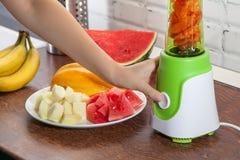 Mädchen mischt in der Mischmaschinenwassermelone, -kantalupe und -bananen Lizenzfreie Stockfotos