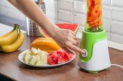Mädchen mischt in der Mischmaschinenwassermelone, -kantalupe und -bananen Stockfoto