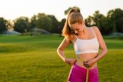 Mädchen misst die Taille mit messendem Band auf der Natur Stockbilder