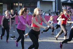Mädchen mit Adidas-Logo auf der Hand, die Übung, hörendes t tut Stockfotografie