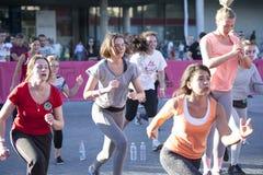 Mädchen mit Adidas-Logo auf der Hand, welche die Übung, hörend auf tut Stockfoto