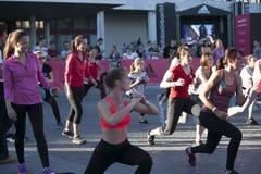 Mädchen mit Adidas-Logo auf der Hand, welche die Übung, hörend auf tut Stockfotografie