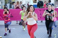 Mädchen mit Adidas-Logo auf der Hand, welche die Übung, hörend auf tut Stockbilder