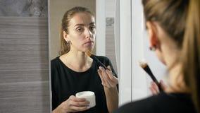 Mädchen mit Akne auf dem Gesicht ist ein Badezimmer durch den Spiegel stock video