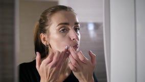 Mädchen mit Akne auf dem Gesicht ist ein Badezimmer durch den Spiegel stock footage