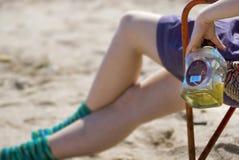 Mädchen mit Alkohol auf Strand Stockfotografie