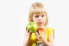 Mädchen mit Apfel in der Hand auf einem grauen Hintergrund Stockfotos