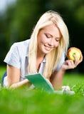 Mädchen mit Apfel liest das Buch, das auf dem Gras liegt Lizenzfreie Stockfotos
