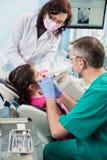 Mädchen mit auf dem ersten zahnmedizinischen Besuch Älterer pädiatrischer Zahnarzt mit der Krankenschwester, die geduldige Zähne  lizenzfreie stockfotos