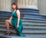 Mädchen mit ausgezeichneter curvy Form führt seine Beine unter langen Abendkleidern 1 vor Lizenzfreie Stockfotografie