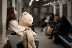 Mädchen mit Bären in einem U-Bahnauto stockbild