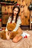 Mädchen mit Bären in ihrer Hand, die im Raum mit hölzernen Wänden sitzt Lizenzfreies Stockbild