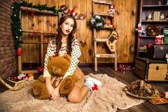 Mädchen mit Bären in ihrer Hand, die im Raum mit hölzernen Wänden sitzt Stockfoto